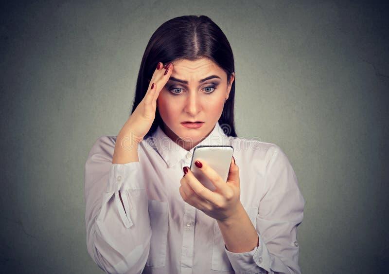 A virada chocou a mulher séria que olha seu telefone celular fotos de stock royalty free