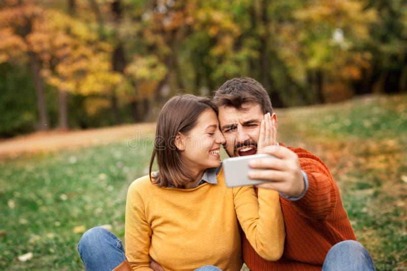 Virada do homem novo que olha o fósforo de futebol sobre o telefone foto de stock