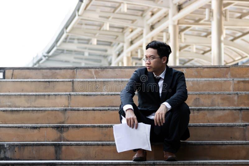 A virada forçou o homem de negócio asiático novo que senta-se em escadas e que sofre da depressão severa Desemprego e conceito da fotos de stock