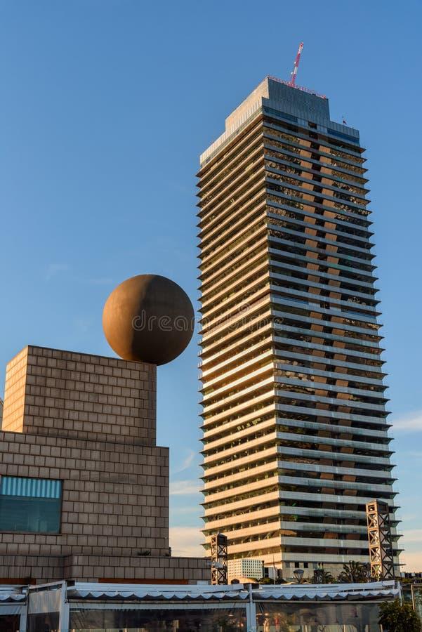 Vire el rascacielos hacia el lado de babor olímpico con la escultura grande de la esfera, arquitectura de Barcelona imagen de archivo libre de regalías