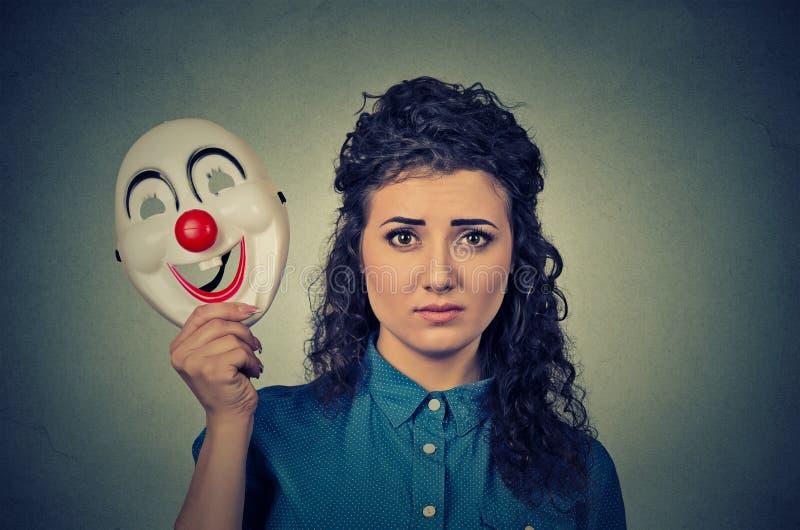 Vire a mulher preocupada com a expressão triste que guarda a máscara do palhaço que expressa a alegria imagens de stock royalty free