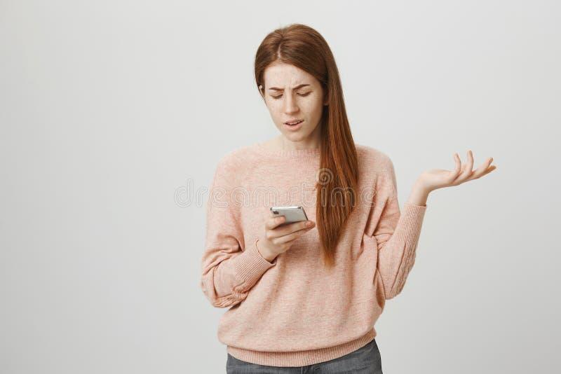 Vire ou irrite a menina do gengibre que gesticula ao olhar a tela do smartphone, sendo à nora ou incomodado e estar foto de stock royalty free