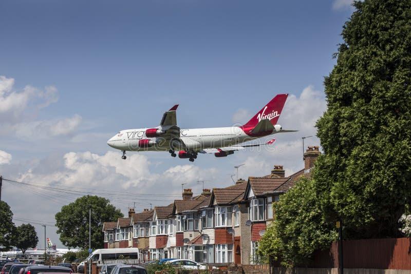 Virgin Atlantic-Vliegtuig die over huizen landen royalty-vrije stock afbeelding