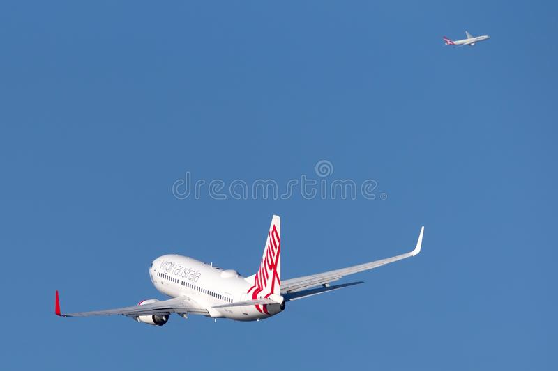 Virgin Australia Airlines Boeing 737 airliner taking off from Sydney Airport with a Qantas A330 in the background. Sydney, Australia - October 7, 2013: Virgin stock photography