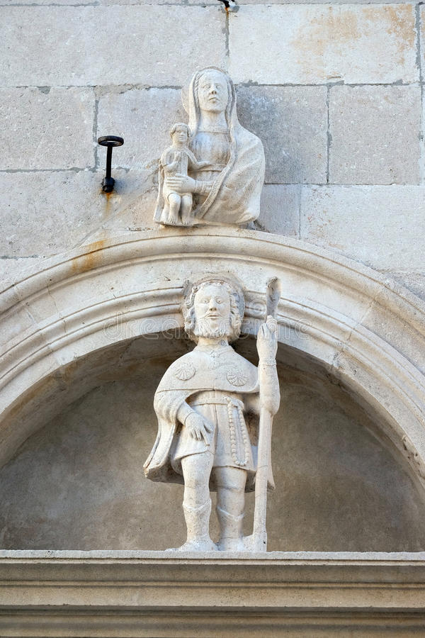 Virgin Mary with baby Jesus and St. Roch. Statues of Virgin Mary with baby Jesus and St. Roch on the St Mark s Cathedral in the historic city Korcula at the stock photos