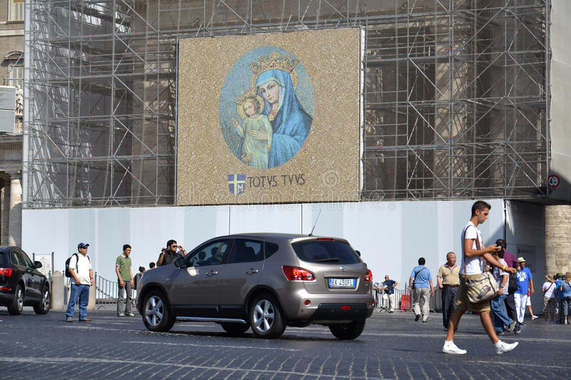 Virgin Mary with Jesus Christ – Totaly yours. Rome, Italy - July 11, 2012: Tourists take pictures in front of reconditioned facade at Saint Peter's Square royalty free stock photo