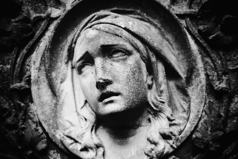 Virgin Mary statue. Vintage statue of sad woman in grief Religion, faith, suffering, love concept stock photos