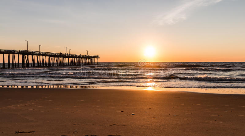 Virginia beach fishing pier with sun at horizon stock for Va fishing license price