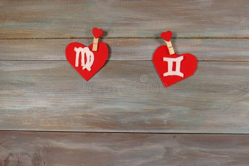 Virgo y gemelos muestras del zodiaco y del corazón Backgroun de madera fotos de archivo
