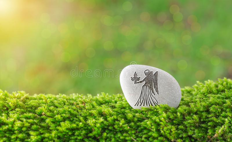 Virgo zodiac symbol in stone. On grass with nature bokeh light background royalty free stock photography