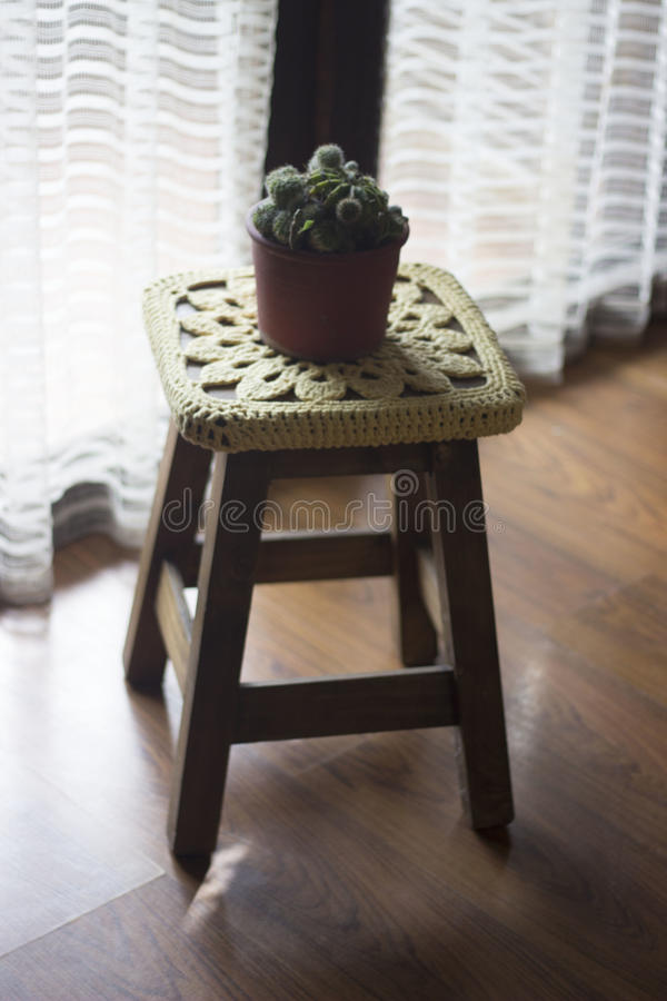 Virka garnering över en träbänk med en kaktus överst royaltyfria bilder
