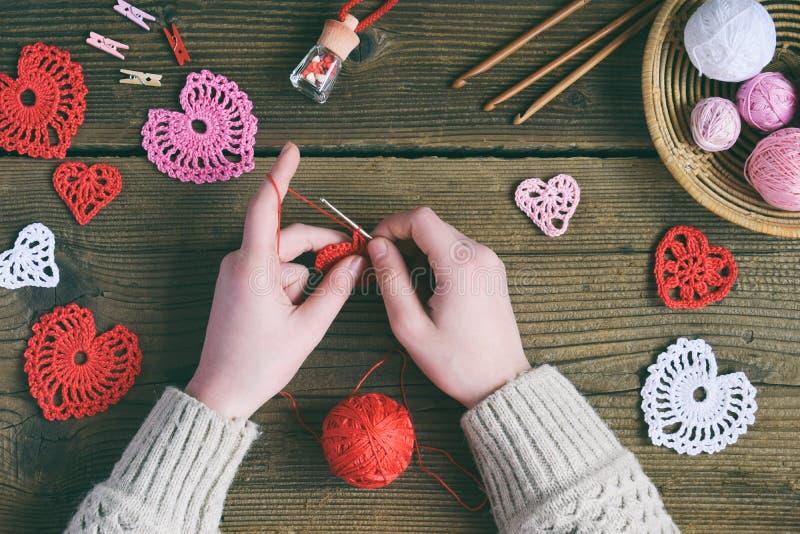 Virka openwork hjärtor Framställning av handgjord garnering Valentindaghantverk Barns DIY, hobbybegrepp, gåva med dina egna royaltyfri fotografi