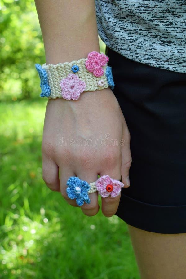 Virkade dina egna smycken Rosa färger och blåttarmband och hårlock på ung flicka Moment 3 - färdigt gods DIY-projekt affär isoler fotografering för bildbyråer