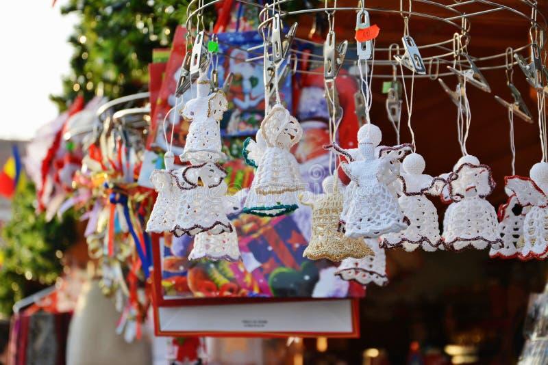 Virkat julpynt hänger på en ställning på julmarknaden arkivbild
