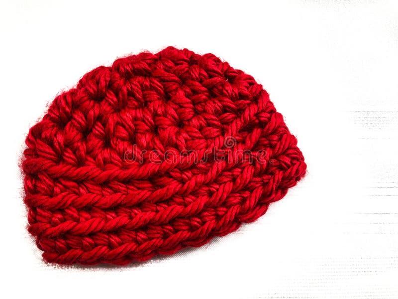 Virkat rött behandla som ett barn locket i klumpigt garn royaltyfri bild