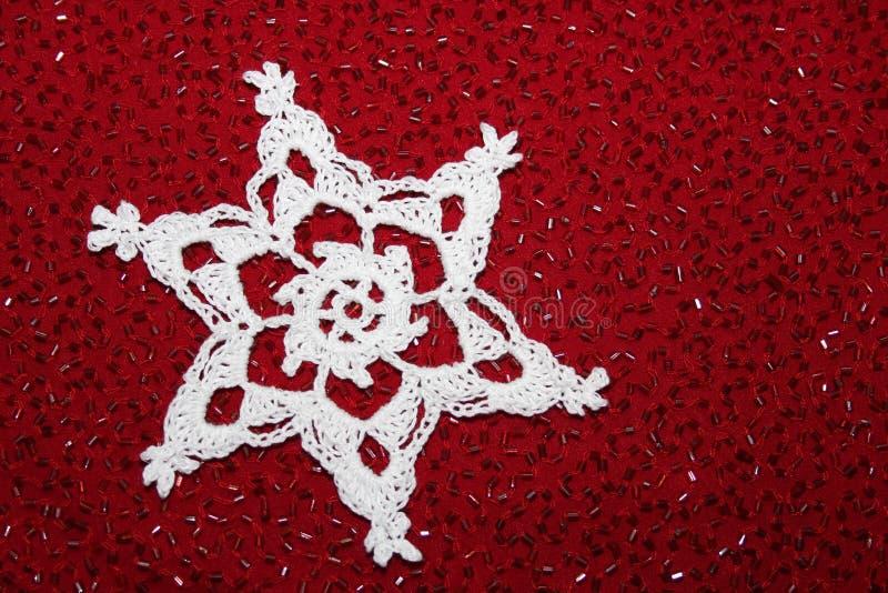 Virkning snör åt snöflingan med röd prydd med pärlor bakgrund arkivbild