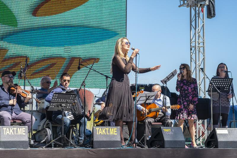 Woman singer sings into a microphone. Virpazar, Montenegro, March, 24, 2019: Public festivity of wine and fish in the Montenegrin town Virpazar. In the park on stock photography