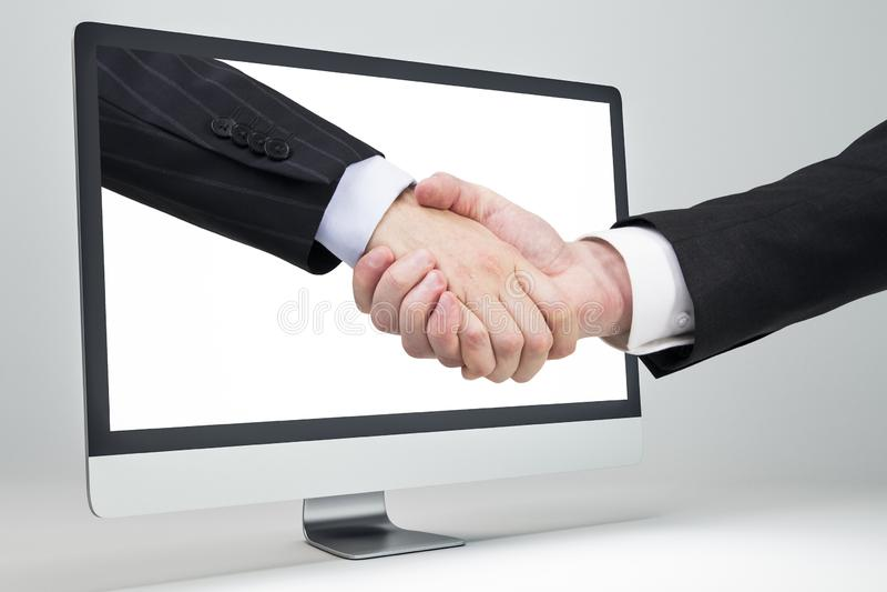 Virtual handshake. Business handshake through a computer screen. Virtual handshake and internet business concept royalty free stock photo