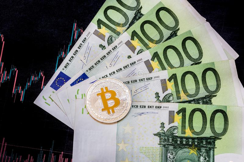 Virtual money golden bitcoin on hundred euro bills and paper forex chart background. Exchange bitcoin cash for a euro royalty free stock photography