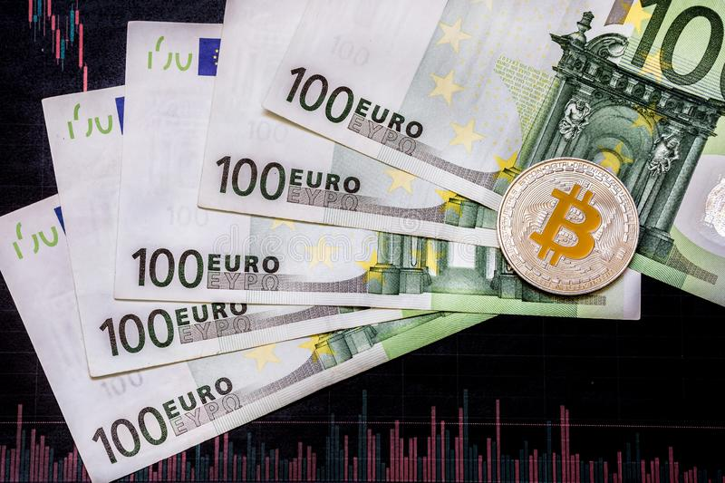 Virtual money golden bitcoin on hundred euro bills and paper forex chart background. Exchange bitcoin cash for a euro stock photo