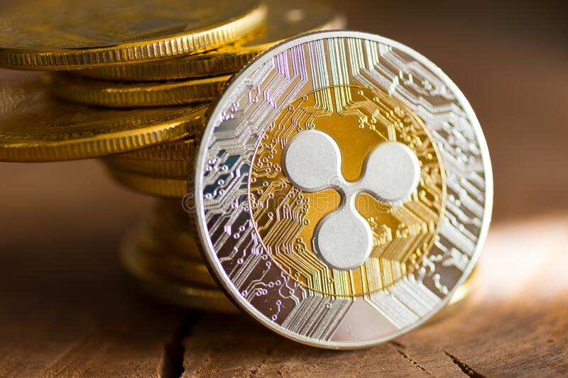 Virtual money Ripple cryptocurrency - pile of coins and gold XRP coin on the wooden background stock photos