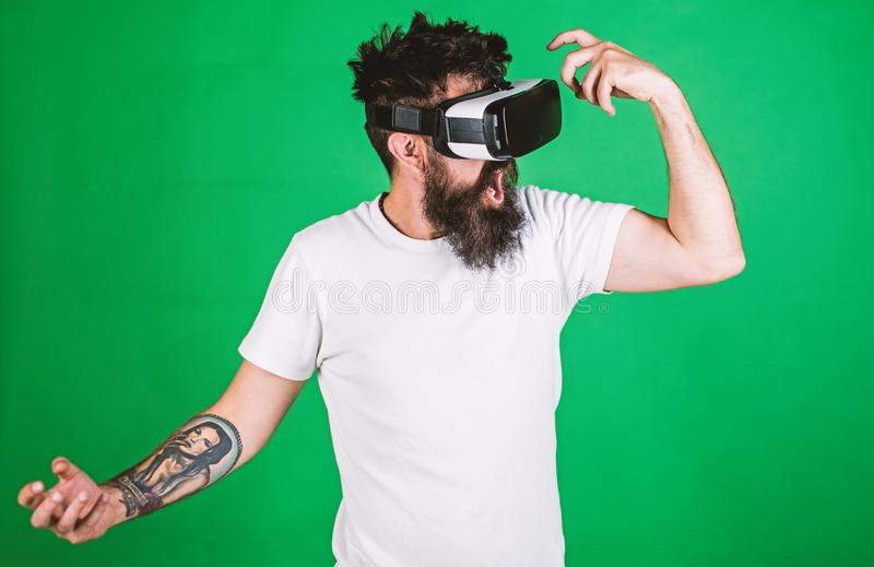 Virtual party concept. Hipster on shouting face having fun in virtual reality. Guy with head mounted display dance in stock photo
