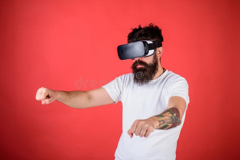 Virtual racing concept. Hipster on confident face driving bike on high speed in virtual reality. Man with beard in VR royalty free stock images