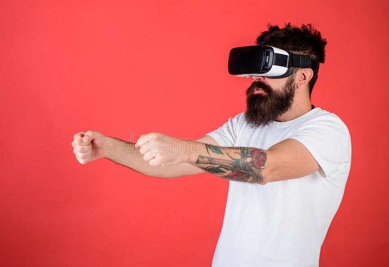 Virtual racing concept. Man with beard in VR glasses driving car, red background. Hipster on concentrated face driving stock images