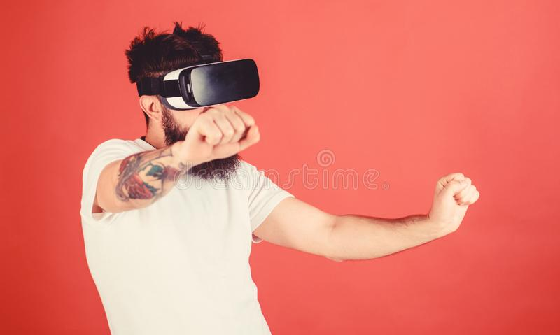 Virtual racing concept. Man with beard in VR glasses driving motorbike, red background. Hipster on confident face stock image