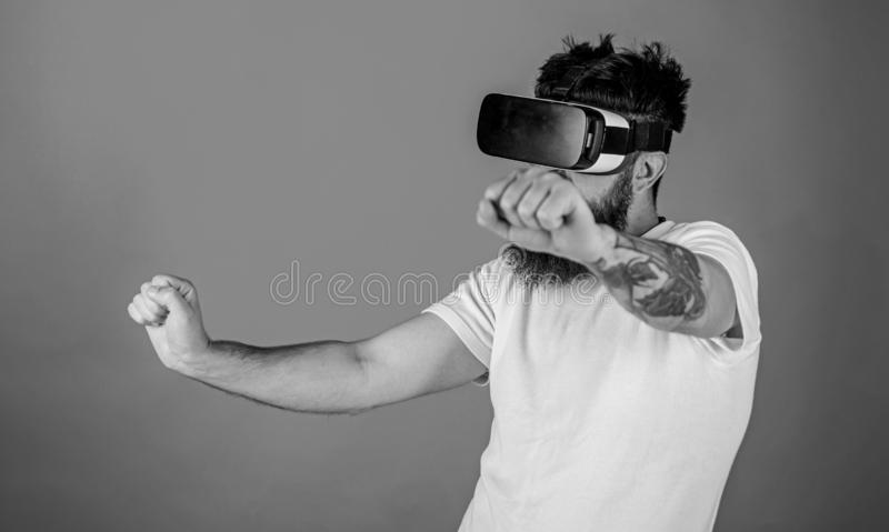 Virtual racing concept. Man with beard in VR glasses driving motorbike, red background. Hipster on confident face stock images