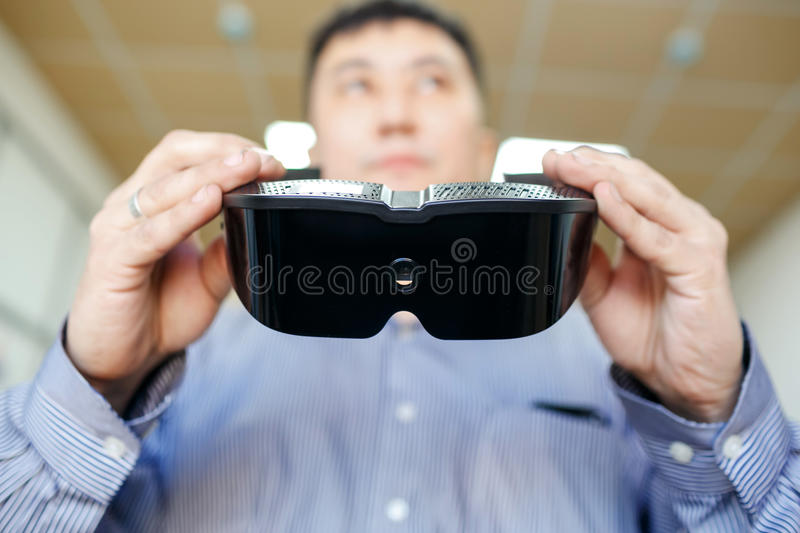 Virtual reality headset close up in hands of man who is going to wear them, vr future concept and new technologies. Virtual reality headset close up in the royalty free stock photo