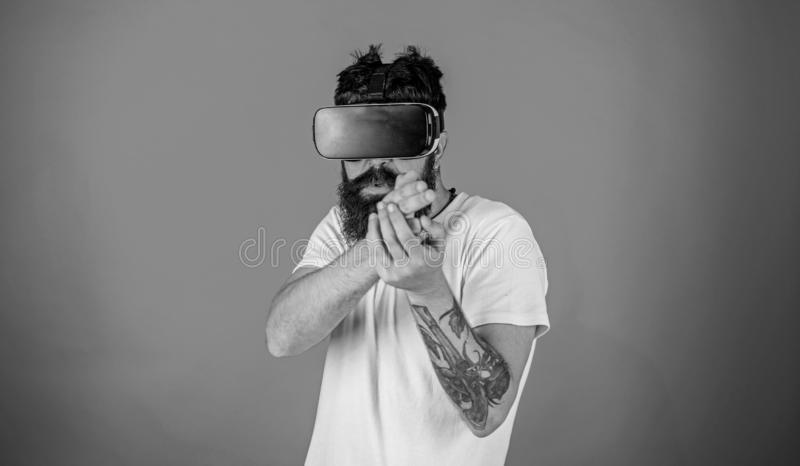 Virtual shooting gallery concept.Guy with head mounted display shoot with gun in virtual reality. Man with beard in VR. Glasses shooting, red background stock photography