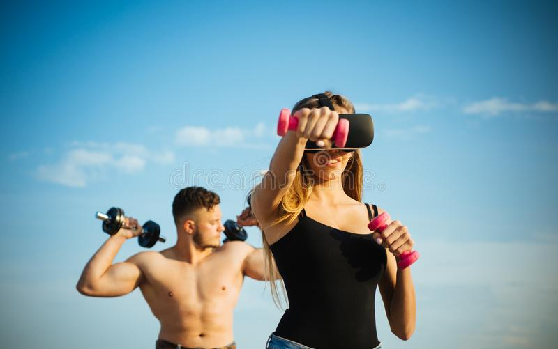 Virtual vision glasses. Woman use virtual simulator for fitness training. Virtual headset and gym equipment. In my royalty free stock image