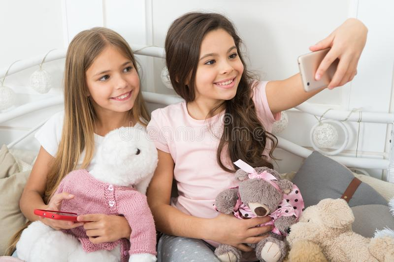 Virtual world. Little girls use phone in bed. Taking Christmas and New Year selfie with smartphone. Happy little. Children with mobile phone. Merry Christmas stock photos