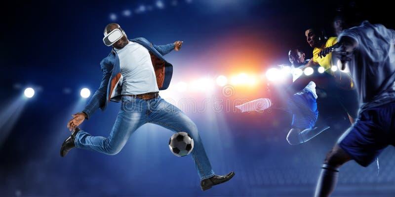Virtuell verkligheth?rlurar med mikrofon p? en svart man som spelar fotboll Blandat massmedia arkivbild
