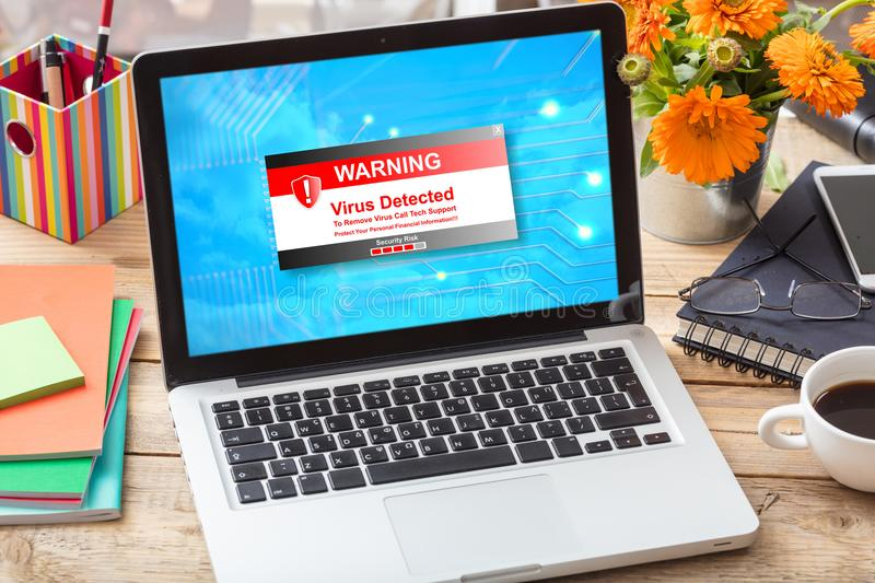 Virus detected warning on a laptop screen on an office desk stock image