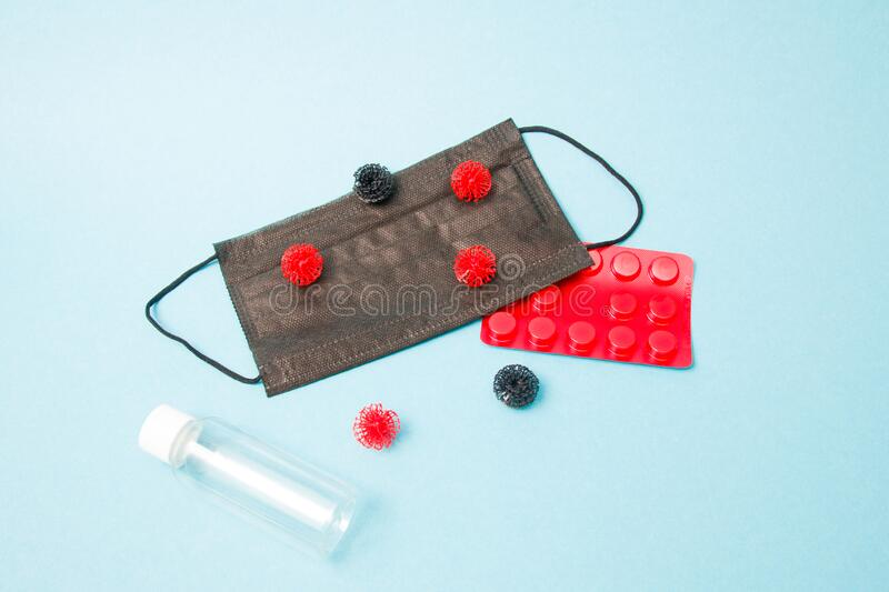 Virus models. On a black medical protective mask, antiseptic bottle, pills in red bluster, blue background, copy space, coronavirus 2020, top view royalty free stock photography