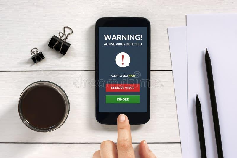 Virus waakzaam op het smartphonescherm met bureauvoorwerpen royalty-vrije stock foto