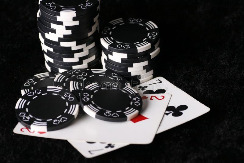 Virutas del juego y la mano de póker posible peor foto de archivo