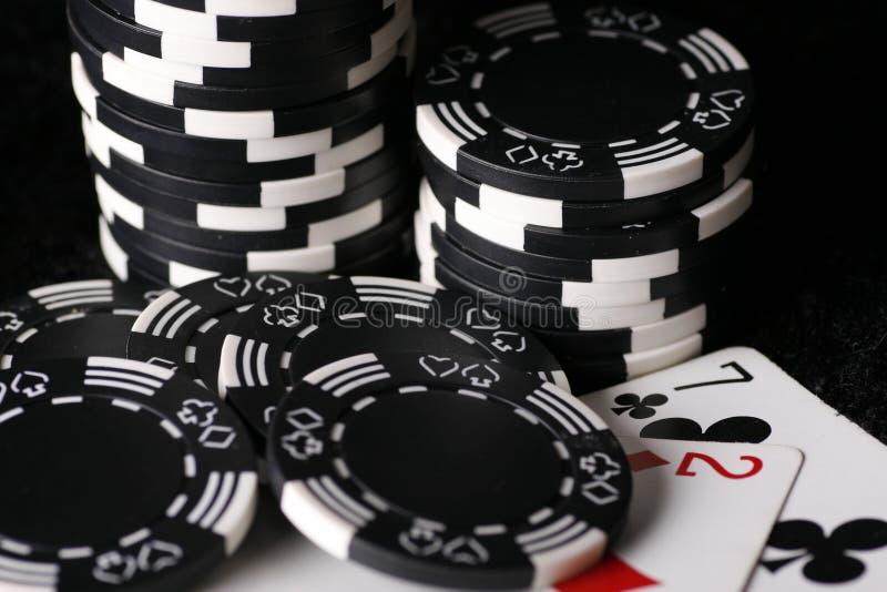 Virutas del juego y la mano de póker posible peor imagenes de archivo