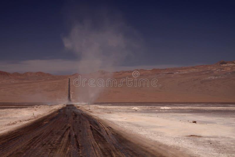 Virvel i horisonten av den ändlösa grusvägen till och med den förlorade karga nivån i den Atacama öknen, Chile arkivbild