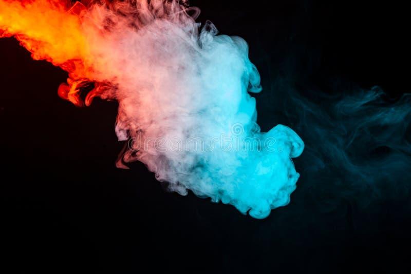 Virvlande runt isolerad kulör rök: blått rött, apelsin som är rosa; Bläddra på en svart bakgrund i det mörka slutet upp Injektion fotografering för bildbyråer