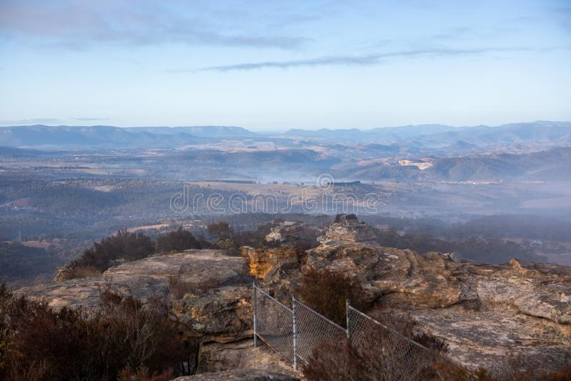A visão das montanhas circundantes e do nevoeiro nos vales, a partir de Hassans Walls Lithgow, Nova Austrália do Sul de Gales, e foto de stock royalty free