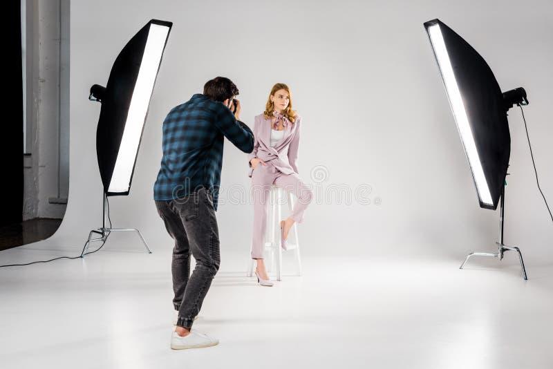 visão de fundo do fotógrafo fotografando linda jovem modelo foto de stock royalty free