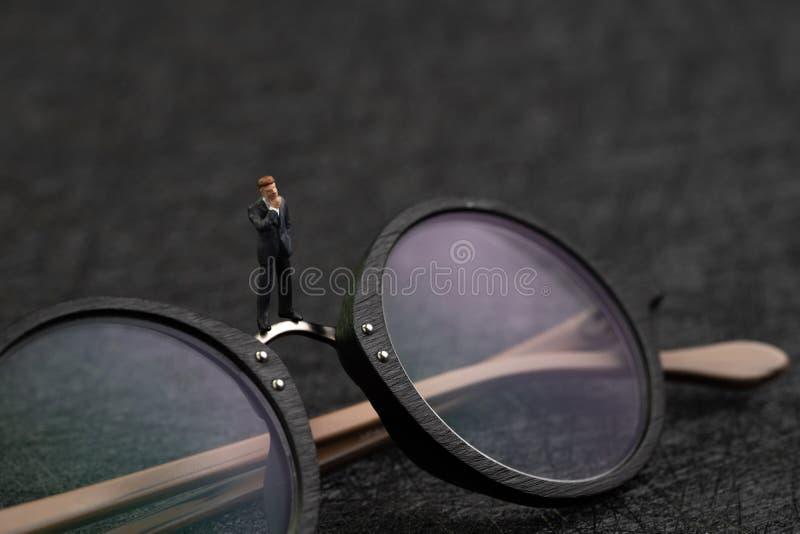 Visão do negócio, pensamento profissional para ver a solução para problemas, homem de negócios diminuto com terno que pensa seria imagens de stock royalty free