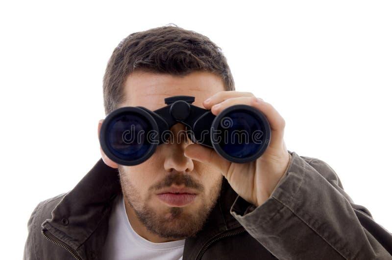 Visão masculina séria através dos binóculos imagem de stock royalty free