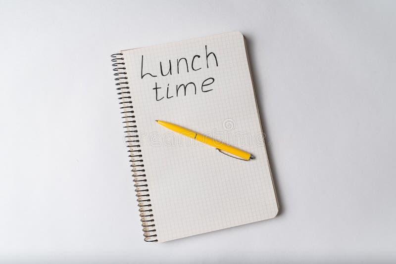 Visão superior do notebook com inscrição LUNCH TIME Copibook e caneta fotografia de stock royalty free