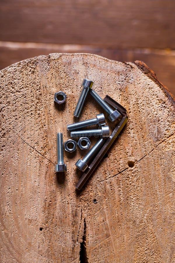 Vis à tête hex, écrou et clé d'hexagone sur un fond en bois photographie stock