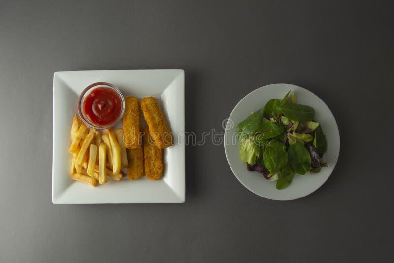 Vis met patat met groene salade Ongezond en gezond voedsel stock fotografie