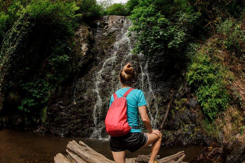Vis-oog fotomeisje die zich op de winkelhaak bevinden die de mooie waterval in het bos bekijken stock fotografie